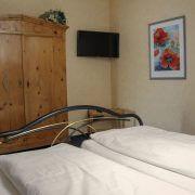 Doppelbett und Fernseher in einem Hotelzimmer im Hotel Schatulle aus Laufersweiler im Hunsrück