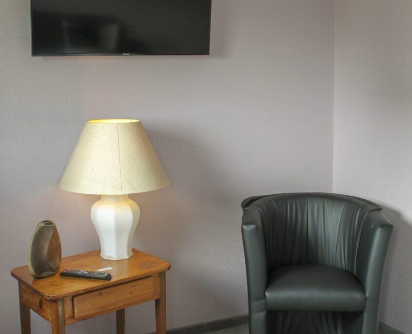 Hotelzimmer mit Fernseher und Sitzmöglichkeit im Hotel Schatulle aus Laufersweiler